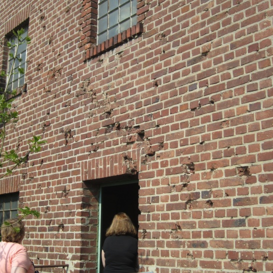 Bullet holes remain on the back wall of the mill.