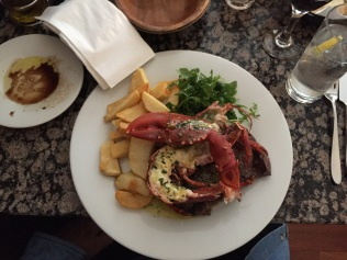 Half a lobster on an 8oz ribeye steak with chips and rocket salad (arugula).